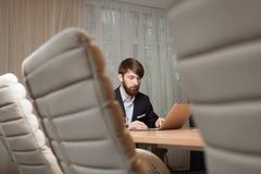 Uomo d'affari che per mezzo del computer portatile Immagini Stock
