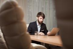 Uomo d'affari che per mezzo del computer portatile Immagine Stock