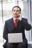 Uomo d'affari che per mezzo del computer portatile e del telefono mobile all'esterno Fotografia Stock