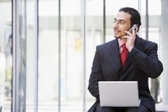 Uomo d'affari che per mezzo del computer portatile e del telefono mobile all'esterno Immagini Stock