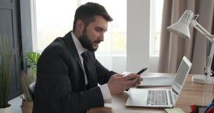 Uomo d'affari che per mezzo del computer portatile e del telefono cellulare all'ufficio video d archivio