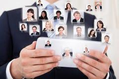 Uomo d'affari che per mezzo del ridurre in pani digitale Fotografie Stock