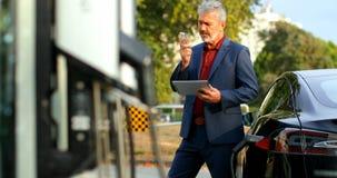 Uomo d'affari che per mezzo della compressa digitale mentre parlando sul telefono cellulare alla stazione di carico 4k stock footage