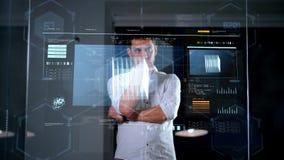 Uomo d'affari che per mezzo della parete di vetro all'ufficio di notte video d archivio
