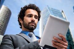 Uomo d'affari che per mezzo di un calcolatore del ridurre in pani Fotografia Stock