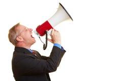 Uomo d'affari che per mezzo di un megafono Fotografie Stock