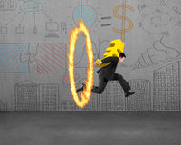 Uomo d'affari che porta euro segno dorato che salta attraverso il cerchio del fuoco Fotografia Stock Libera da Diritti