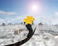 Uomo d'affari che porta il pezzo di puzzle dell'oro 3D che equilibra sul cavo Immagini Stock
