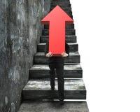 Uomo d'affari che porta il segno rosso della freccia che scala sulle scale Immagine Stock Libera da Diritti