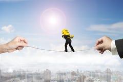 Uomo d'affari che porta la corda per funamboli d'equilibratura dell'euro segno con le mani noiose Fotografia Stock