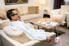 Uomo d'affari che porta un accappatoio nella camera di albergo, sedendosi nella poltrona e nella conversazione Immagini Stock