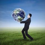Uomo d'affari che porta un globo fotografia stock