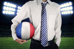 Uomo d'affari che porta un pallone da calcio al campo Immagine Stock