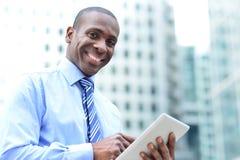 Uomo d'affari che posa con la compressa digitale immagine stock libera da diritti