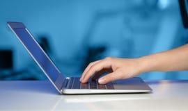 Uomo d'affari che preme computer portatile moderno sul backgrou variopinto Fotografia Stock Libera da Diritti