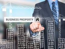 Uomo d'affari che preme il bottone della proprietà di affari sugli schermi virtuali Fotografie Stock