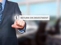 Uomo d'affari che preme il bottone di ritorno su investimento su scre virtuale immagini stock libere da diritti
