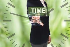 Uomo d'affari che preme il bottone di tempo sugli schermi virtuali e sull'orologio Immagine Stock