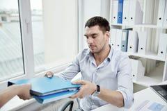 Uomo d'affari che prende cartella da segretario in ufficio fotografie stock