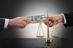 Uomo d'affari che prende dono davanti alla scala della giustizia Fotografia Stock Libera da Diritti