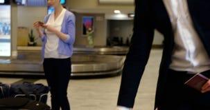 Uomo d'affari che prende i suoi bagagli fuori dal carosello del bagaglio archivi video