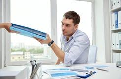 Uomo d'affari che prende le carte da segretario in ufficio fotografia stock