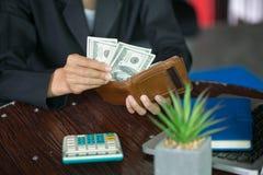 Uomo d'affari che prende soldi dal suo portafoglio, dal portafoglio della mano dell'uomo e dai soldi sulla tavola fotografia stock libera da diritti