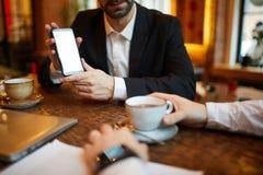 Uomo d'affari che presenta Smartphone fotografie stock