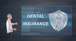 Uomo d'affari che presenta un concetto dell'assicurazione dentale su uno schermo della parete Immagine Stock