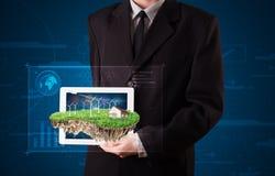 Uomo d'affari che presenta una terra perfetta di ecologia con una casa e w Fotografie Stock