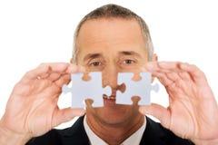 Uomo d'affari che prova a collegare i pezzi di puzzle Immagine Stock Libera da Diritti