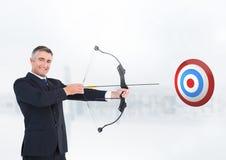 Uomo d'affari che punta sul bordo dell'obiettivo contro il fondo bianco Fotografia Stock