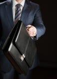 Uomo d'affari che raggiunge fuori cartella di cuoio Immagini Stock