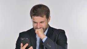 Uomo d'affari che reagisce alla perdita mentre per mezzo dello smartphone video d archivio