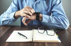 Uomo d'affari che regola il suo orologio Concetto di affari fotografie stock