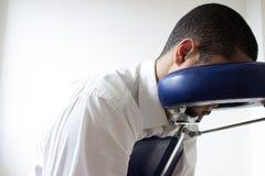 Uomo d'affari che riceve shiatsu su una sedia di massaggio fotografie stock libere da diritti