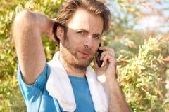 Uomo d'affari che riceve telefonata durante l'allenamento all'aperto Fotografia Stock