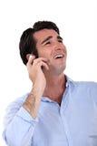 Uomo d'affari che ride sopra il telefono. Fotografie Stock