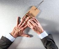 Uomo d'affari che rimuove il suo mano una trappola del topo con la banconota Fotografie Stock Libere da Diritti