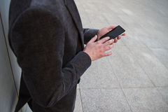 Uomo d'affari che riposa dal lavoro e mentre inviando dai messaggi e parlando con il suo smartphone Fotografia Stock