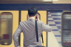 Uomo d'affari che rivolge al telefono alla stazione ferroviaria Fotografia Stock