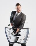 Uomo d'affari che rompe un orologio Fotografia Stock