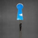 Uomo d'affari che scala per chiudere a chiave la porta di forma con cielo blu fuori Immagine Stock