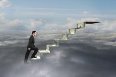 Uomo d'affari che scala sulle scale dei soldi con il cloudscape naturale del cielo Fotografie Stock