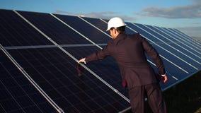 Uomo d'affari che sceglie energia alternativa, camminante alla stazione a energia solare archivi video