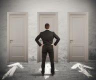 Uomo d'affari che sceglie la porta giusta Fotografie Stock Libere da Diritti