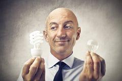 Uomo d'affari che sceglie lampadina differente due fotografie stock
