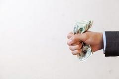 Uomo d'affari che schiaccia le banconote nel bianco isolate fotografie stock
