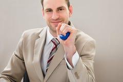 Uomo d'affari che schiaccia stressball blu Fotografia Stock