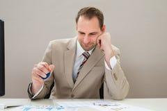 Uomo d'affari che schiaccia stressball blu Fotografie Stock